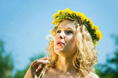 woman in chaplet blowing dandelion against sky photo