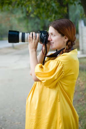 9 months: Portrait of 9 months pregnant woman  with photocamera outdoor