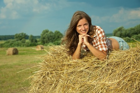 Young woman laying on top of a hay bail photo