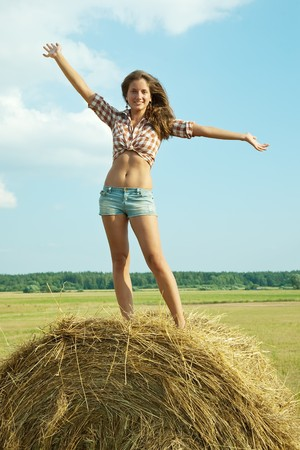 Young girl standing on top of straw bail photo