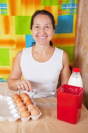 Mature woman with food products for omelette in her kitchen.
