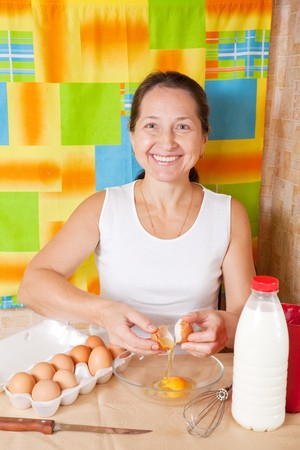 Mature woman adds eggs into dish. One of the stages of cooking  omelet.  See series photo