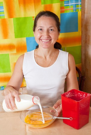 Mature woman adds milk into dish.