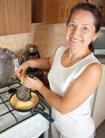 Mature woman grating cheese into scrambled eggs in skillet. One of the stages of cooking  omelet.  See series photo