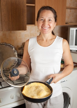 Mature woman with  omelette in skillet at kitchen.