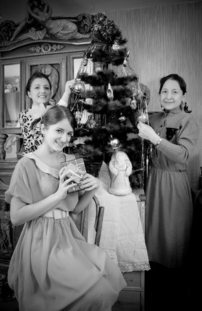 Retro photo of Teen girls with mother decorating Christmas tree at home photo