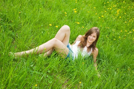 long-haired teen girl is lying at meadow photo