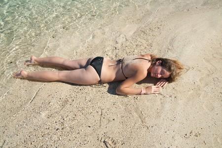 beauty girl in bikini sunbathing at resort beach photo