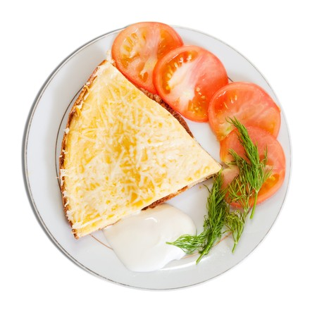 omelette: cheese omelet  garnished with tomato. Isolated over white