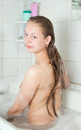 Rear view of girl sitting in bath photo