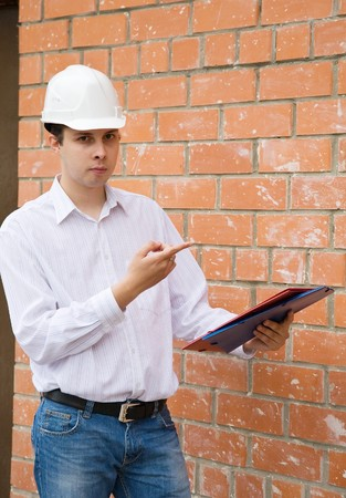 tasker: Happy builder with documents against  the brick wall