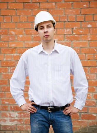 tasker: Man in hard hat  against  the brick wall Stock Photo