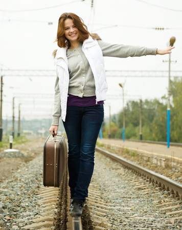Girl with suitcase walking along  railroad rail photo