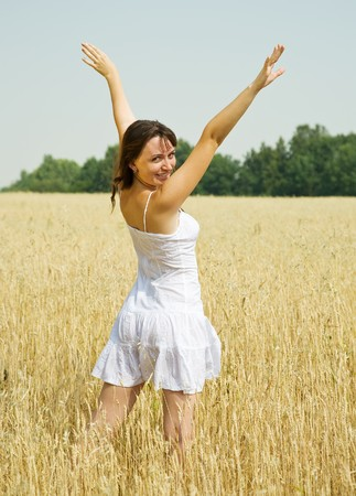 Standing girl  in white at cereals field in summer Stock Photo - 8202260