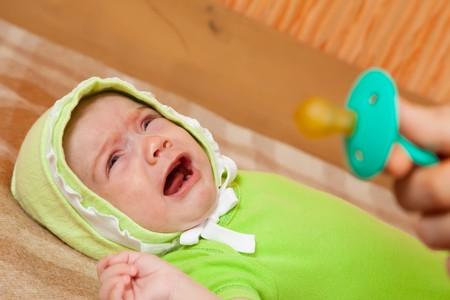 d�livrance: B�b� pleurer sur le lit et la main avec binky