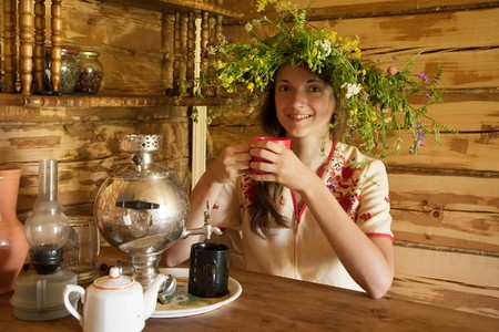 young girl having tea in russian traditional interior photo