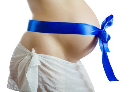 Belly of 9 months pregnant woman with blue ribbon over white photo