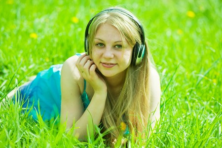 Young   happy girl listening music in headphones on meadow photo