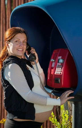 9 months  pregnant woman on the pay phone outdoor Stock Photo - 8202389