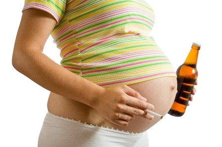 smoking girl: Young pregnant woman holding cigarette and beer. Isolated over white