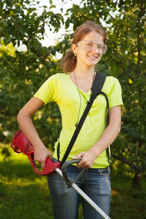 Girl works with cordless grass trimmer in garden Stock Photo - 8202674