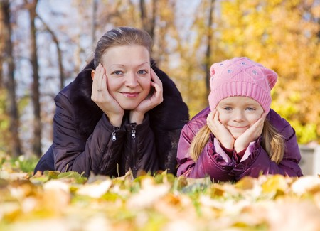 Portrait of woman with her girl in autumn park photo