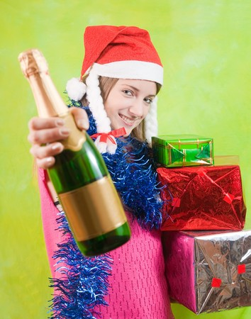 beautiful girl with champagne and  present boxes over green photo