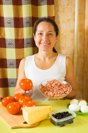 farce: Woman with food products for farci tomato in her kitchen. See in series stages of cooking of farci tomato