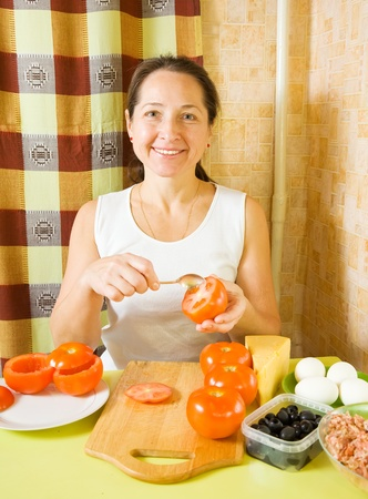 farci: Mature woman making stuffed tomato in her kitchen. See in series stages of cooking of farci tomato  Stock Photo