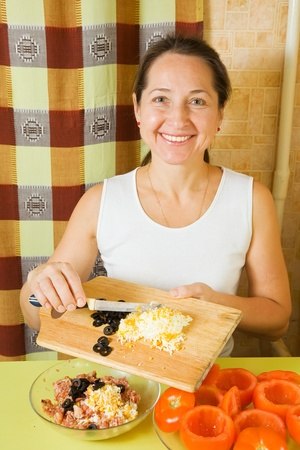 farce: Mature Woman adds grated eggs and  sliced olives in mincemeat. See in series stages of cooking of stuffed tomato Stock Photo