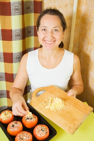 farci: Woman adds cheese to stuffed tomato in her kitchen. See in series stages of cooking of farci tomato
