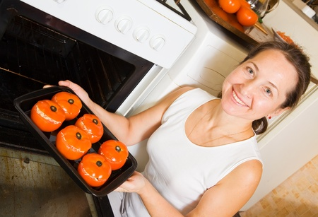 Mature woman roasting farci tomato on pan in oven.