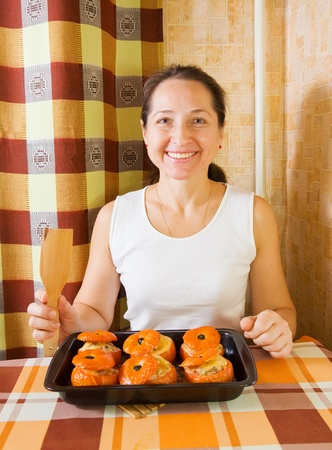 farci: Woman with   roasted farci tomato. See in series stages of cooking of farci tomato