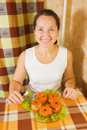 Woman with   roasted stuffed tomato.