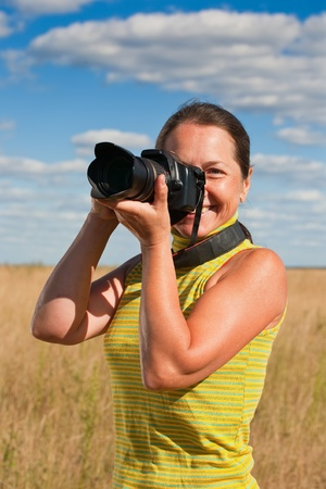 Senior woman taking photo with camera against field photo