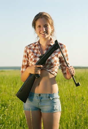 airsoft: beautiful girl holding pneumatic air rifle outdoor