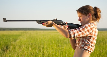 young girl aiming pneumatic air rifle outdoor photo