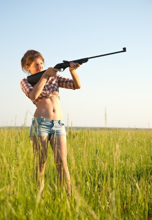 airsoft: young girl aiming pneumatic air rifle outdoor Stock Photo
