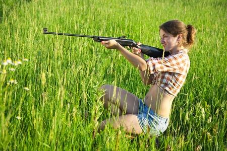 airgun: girl  aiming a pneumatic air rifle  in grass meadow