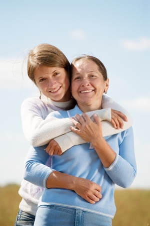 Portrait of mother with teenager daughter against sky photo