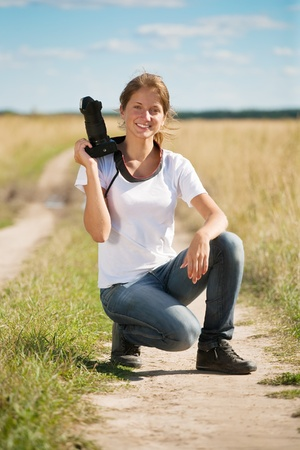 photocamera: girl with photocamera  at field against sky Stock Photo