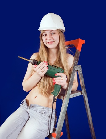 Sexy girl in a hard hat with drill over blue background photo