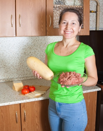 cocozelle: Mature woman with ingredients for stuffed vegetable marrow. See in series stages of cooking of stuffed vegetable marrow