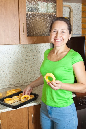 Woman puts vegetable marrow rings into roasting pan.See in series stages of cooking of stuffed vegetable marrow  Stock Photo - 8273637