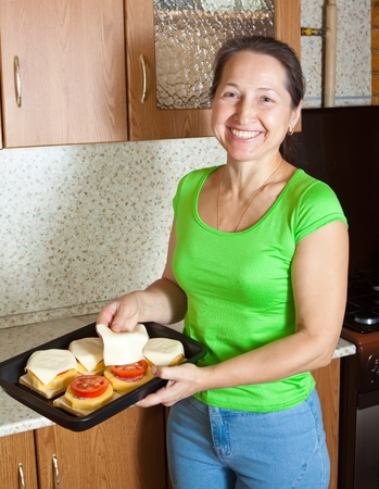 farce: Woman adds cheese to stuffed vegetable marrow in her kitchen. See in series stages of cooking of stuffed vegetable marrow  Stock Photo