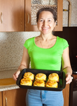cocozelle: Woman with cooked baked stuffed vegetable marrow. See in series stages of cooking of stuffed vegetable marrow