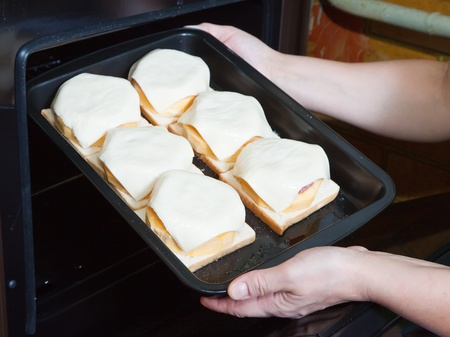 cocozelle: Closeup of cook hands putting  stuffed vegetable marrow into oven. See in series stages of cooking of stuffed vegetable marrow Stock Photo