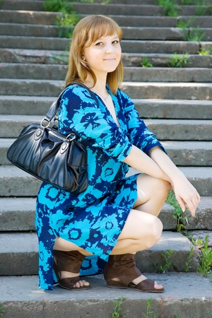 Girl in blue dress on stairs in summer day