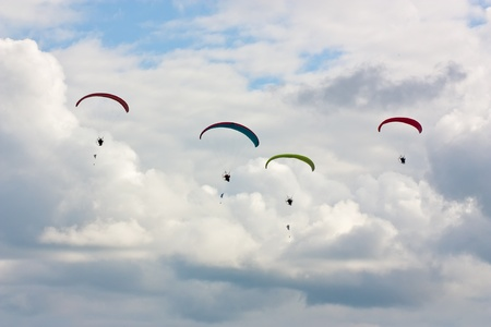 parapendio: Four paragliders  soaring against cloudy sky  in summer Stock Photo