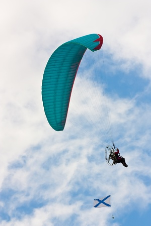 parapendio: Paraglider with flag soaring against cloudy sky